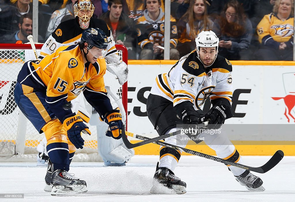 Adam McQuaid #54 of the Boston Bruins clears the puck from the stick of Craig Smith #15 of the Nashville Predators at Bridgestone Arena on December 23, 2013 in Nashville, Tennessee.