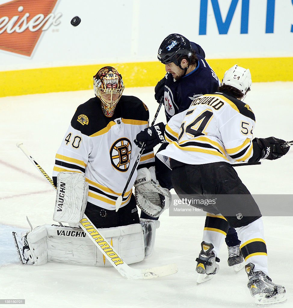 <a gi-track='captionPersonalityLinkClicked' href=/galleries/search?phrase=Adam+McQuaid&family=editorial&specificpeople=2238883 ng-click='$event.stopPropagation()'>Adam McQuaid</a> #54 of the Boston Bruins puts pressure on <a gi-track='captionPersonalityLinkClicked' href=/galleries/search?phrase=Tanner+Glass&family=editorial&specificpeople=4596666 ng-click='$event.stopPropagation()'>Tanner Glass</a> #15 in front of Bostonh goalie <a gi-track='captionPersonalityLinkClicked' href=/galleries/search?phrase=Tuukka+Rask&family=editorial&specificpeople=716723 ng-click='$event.stopPropagation()'>Tuukka Rask</a> #40 in NHL action at the MTS Centre on December 6, 2011 in Winnipeg, Manitoba, Canada.