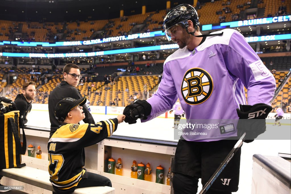 Adam McQuaid #54 of the Boston Bruins wears a Hockey Fights Cancer jersey and fists bumps Liam Fitzgerald the fist bump kid before the game against the Vancouver Canucks at the TD Garden on October 19, 2017 in Boston, Massachusetts.