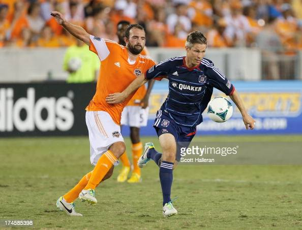 Adam Moffat of the Houston Dynamo battles forthe ball against Logan Pause of the Chicago Fire at BBVA Compass Stadium on July 27 2013 in Houston Texas