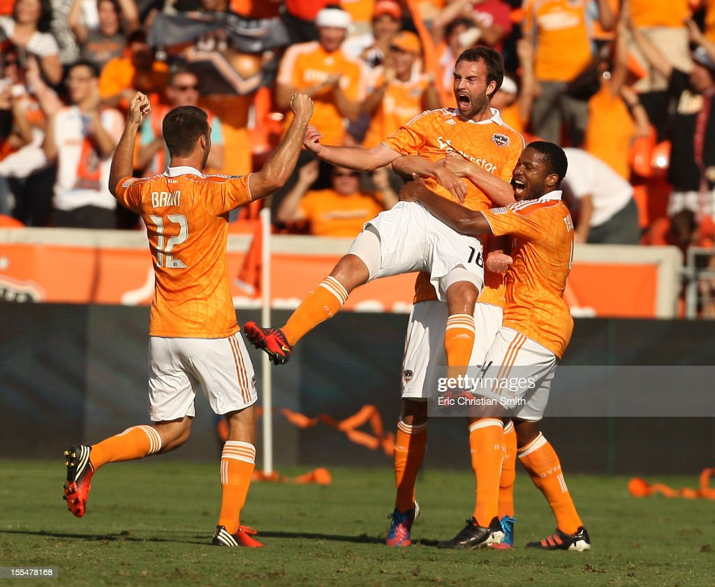 Adam Moffat #16 of the Houston Dynamo celebrates his goal in the 19th minute with teammates <a gi-track='captionPersonalityLinkClicked' href=/galleries/search?phrase=Jermaine+Taylor+-+Soccer+Player&family=editorial&specificpeople=13524207 ng-click='$event.stopPropagation()'>Jermaine Taylor</a> #4 and Will Bruin #12 during the first half of a MLS Eastern Conference Semifinal against Sporting Kansas City at BBVA Compass Stadium on November 4, 2012 in Houston, Texas.