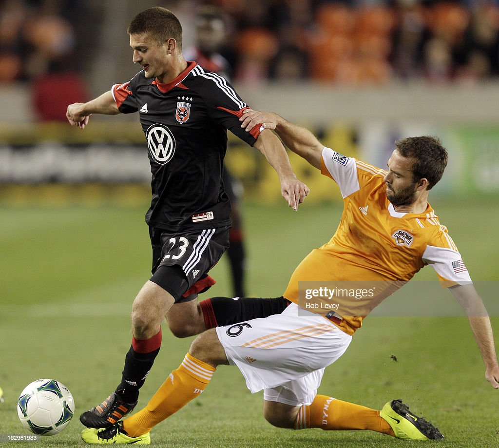 Adam Moffat #16 of the Houston Dynamo makes a sliding tackle on Perry Kitchen #23 of the D.C. United during first half action at BBVA Compass Stadium on March 2, 2013 in Houston, Texas.