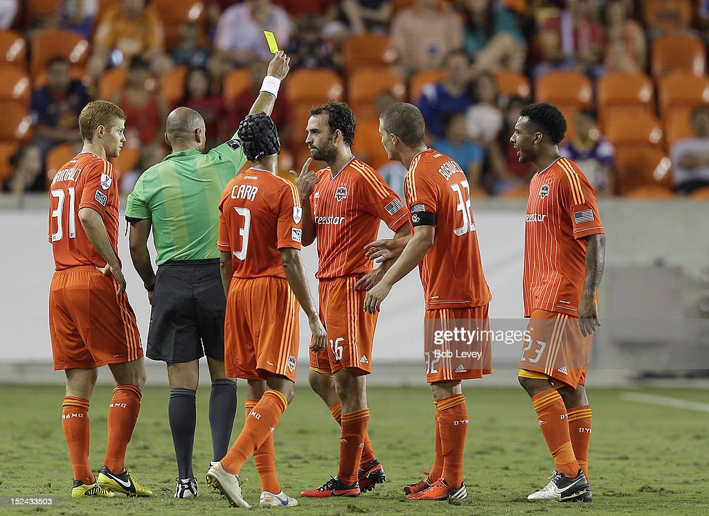 Adam Moffat of the Houston Dynamo receives a yellow card from referee Francisco Chacon at BBVA Compass Stadium on September 20 2012 in Houston Texas...