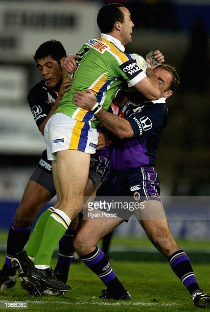Adam Mogg for the Raiders is tackled by Danny Williams and Stephen Kearney for the Storm during the Round nine NRL match between the Melbourne Storm...