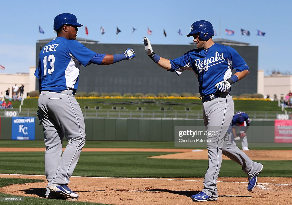 Adam Moore #66 of the Kansas City Royals high-fives Salvador Perez #13 after hitting a solo home run against the Texas Rangers during the fifth inning of the spring training game at Surprise Stadium on February 22, 2013 in Surprise, Arizona.