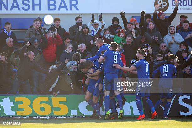 Adam Morgan of Curzon Ashton celebrates with team mates and fans as he scores their third goal and completes his hat trick during the Emirates FA Cup...
