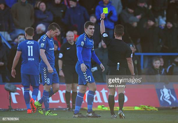 Adam Morgan of Curzon Ashton is booked by referee James Adcock as he celebrates as he scores their third goal and completes his hat trick during the...
