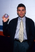 Adam Oates of the Washington Capitals holds up the puck that he got his 1000th career point against the New York Islanders on October 8 1997 at the...