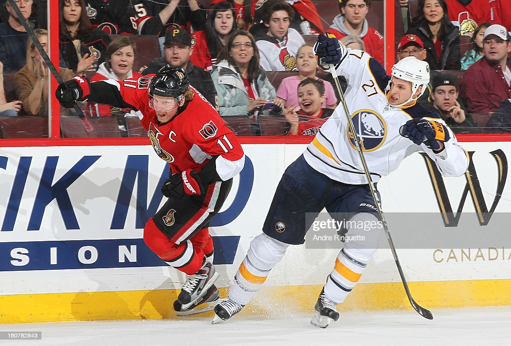 Adam Pardy #27 of the Buffalo Sabres holds up Daniel Alfredsson #11 of the Ottawa Senators along the boards, resulting in a penalty, on February 5, 2013 at Scotiabank Place in Ottawa, Ontario, Canada.