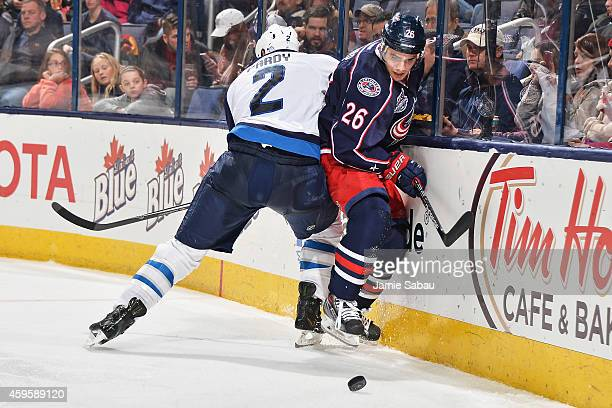 Adam Pardy of the Winnipeg Jets attempts to pin Corey Tropp of the Columbus Blue Jackets against the boards as he follows a loose puck during the...
