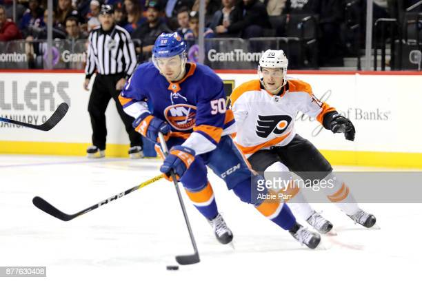 Adam Pelech of the New York Islanders skates with the puck against Danick Martel of the Philadelphia Flyers in the third period during their game at...