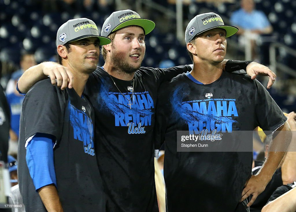 Adam Plutko #9, Cody Regis #18, and Kevin Williams #5 of the UCLA Bruins stand together as they watch a score board highlight video after defeating the Mississippi State Bulldogs during game two of the College World Series Finals on June 25, 2013 at TD Ameritrade Park in Omaha, Nebraska. UCLA won 8-0 to take the series two games to none and win the College World Series Championship.
