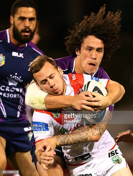 Adam Quinlin of the Dragons is tackled by Kevin Proctor of the Storm during the round 16 NRL match between the St George Illawarra Dragons and the...
