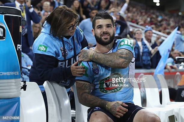 Adam Reynolds of the Blues receives attention from the trainer as he sits on the bench during game two of the State Of Origin series between the...