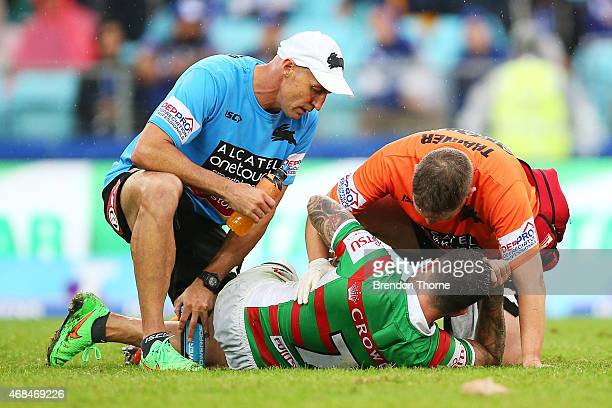 Adam Reynolds of the Rabbitohs receives attention from the trainers after being tackled late by James Graham of the Bulldogs while attempting a field...
