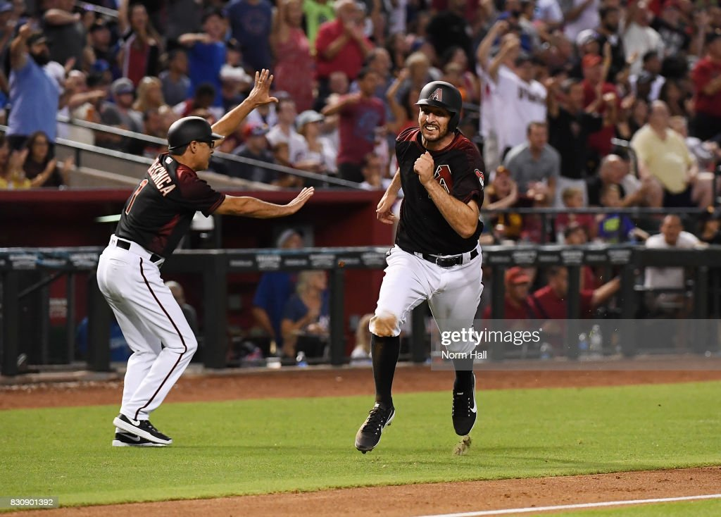 Adam Rosales #9 of the Arizona Diamondbacks rounds third and scores on a JD Martinez #28 double as third base coach Tony Perezchica #1 signals for Paul Goldshmidt #44 to stop at third during the sixth inning against the Chicago Cubs at Chase Field on August 12, 2017 in Phoenix, Arizona.