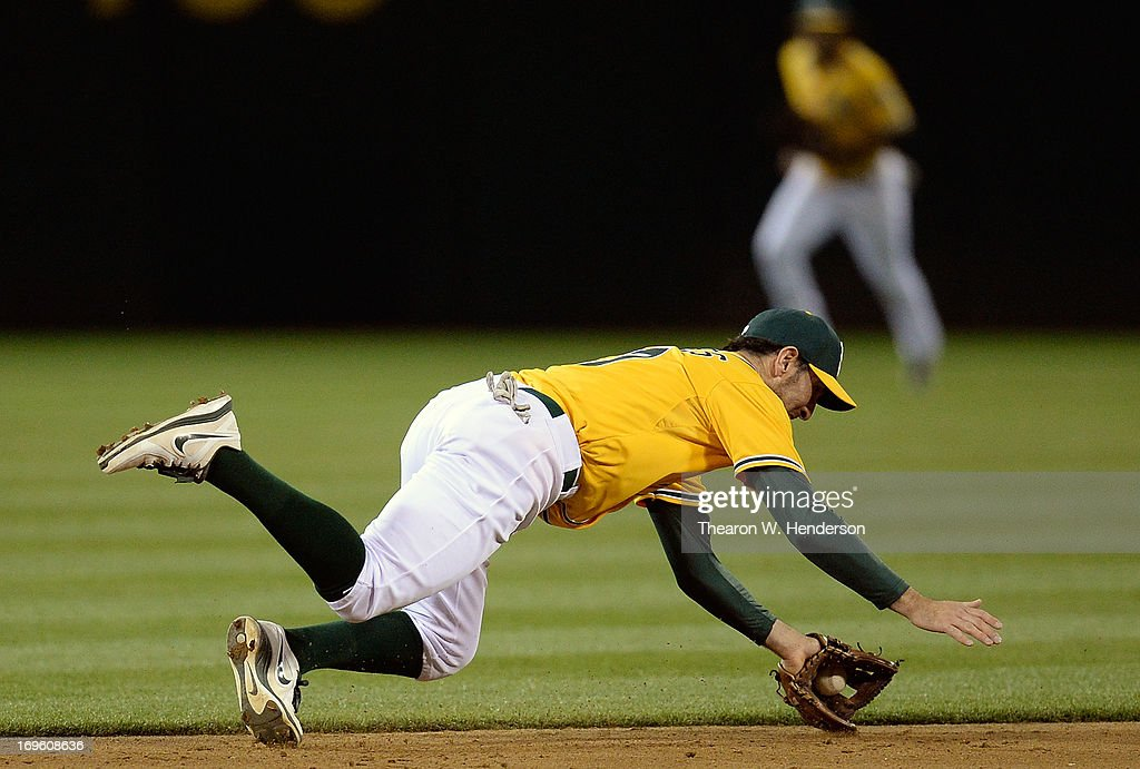 Adam Rosales #17 of the Oakland Athletics dives and takes a hit away from Hunter Pence #8 of the San Francisco Giants in the six inning at O.co Coliseum on May 28, 2013 in Oakland, California.