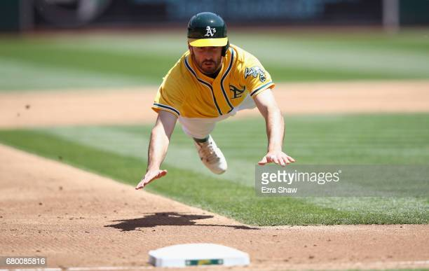 Adam Rosales of the Oakland Athletics dives in to third base after tagging up on a ball hit by Bruce Maxwell in the third inning Detroit Tigers at...