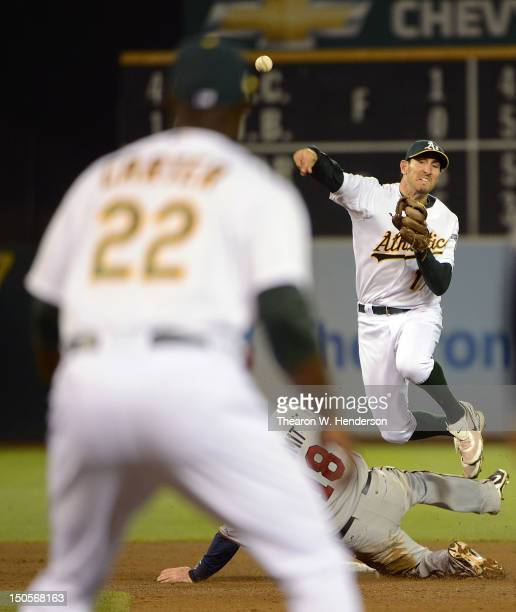 Adam Rosales of the Oakland Athletics gets his throw off to Chris Carter at first base to complete a triple play while avoiding the slide of Ryan...