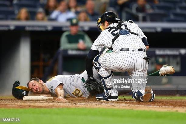 Adam Rosales of the Oakland Athletics is tagged out at home plate by Austin Romine of the New York Yankees in the eighth inning at Yankee Stadium on...