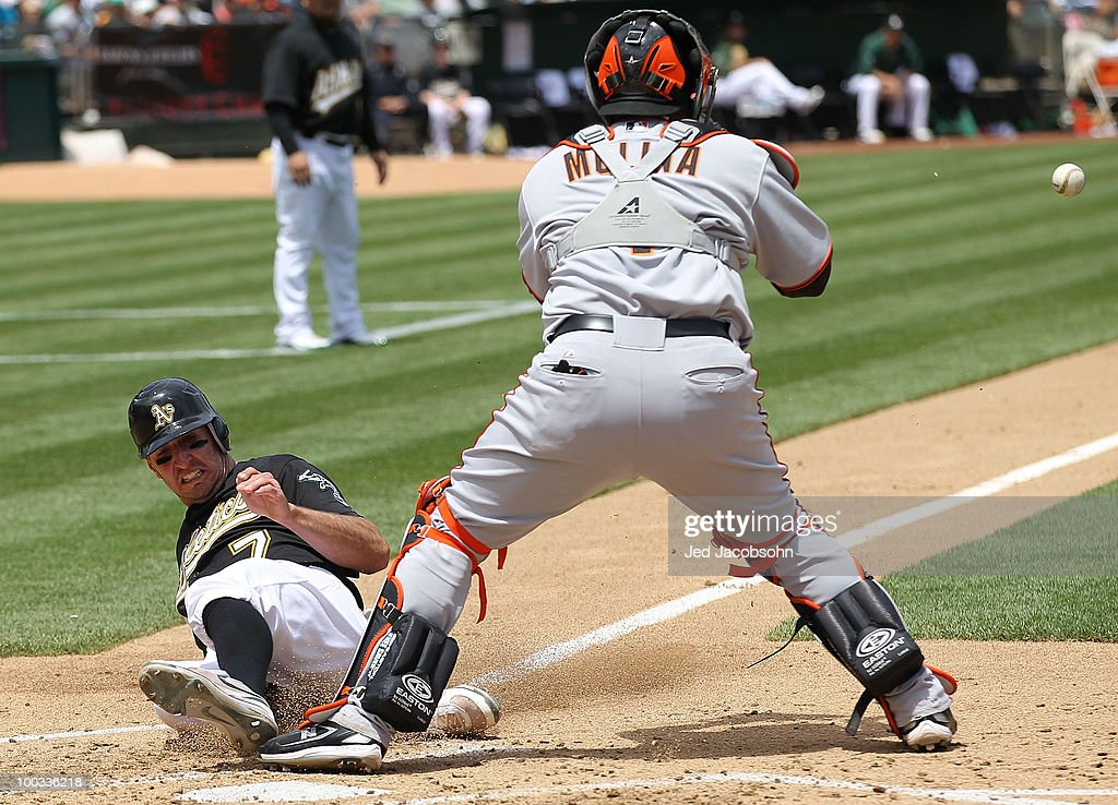 Adam Rosales #7 of the Oakland Athletics slides home safe as Bengie Molina #1 of the San Francisco Giants waits for the throw on a sacrafice fly hit by Coco Crisp in the third inning during an MLB game at the Oakland-Alameda County Coliseum on May 22, 2010 in Oakland, California.