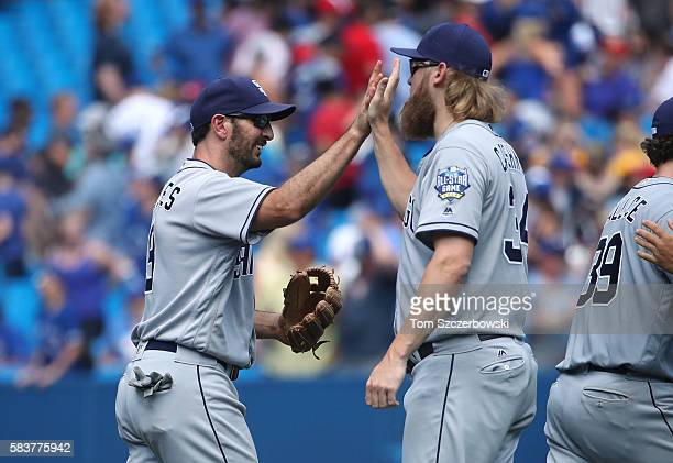 Adam Rosales of the San Diego Padres celebrates their victory with Andrew Cashner during MLB game action against the Toronto Blue Jays on July 27...