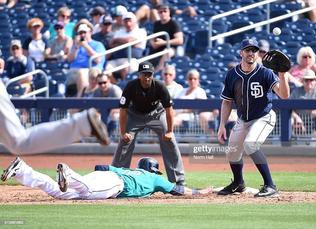 Adam Rosales #9 of the San Diego Padres waits for the ball as Leonys Martin #12 of the Seattle Mariners dives safely back into first base during the fifth inning at Peoria Stadium on March 2, 2016 in Peoria, Arizona.