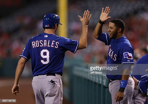 Adam Rosales of the Texas Rangers is congratulated by Elvis Andrus after scoring a run on a tworun home run by Jake Smolinski against the Los Angeles...