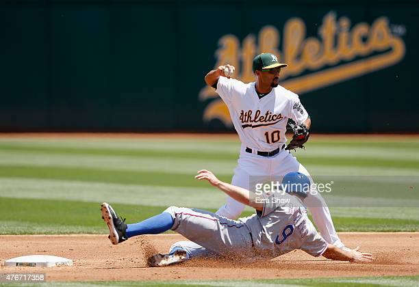 Adam Rosales of the Texas Rangers is forced out at second base as Marcus Semien of the Oakland Athletics tries to turn a double play on a ball hit by...