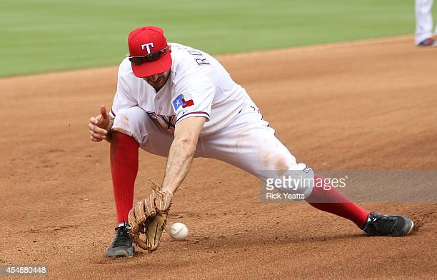 Adam Rosales of the Texas Rangers recover a ball hilt by Robinson Cano of the Seattle Mariners throwing too high for the out on first at Globe Life...