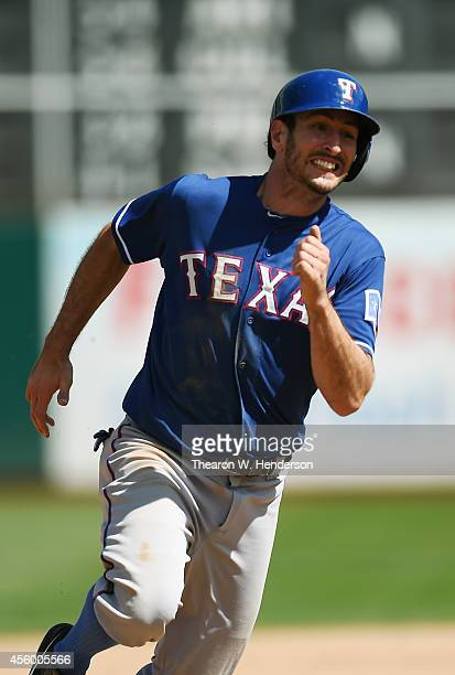 Adam Rosales of the Texas Rangers rounds third to score on an rbi double from Leonys Martin against the Oakland Athletics in the top of the six...