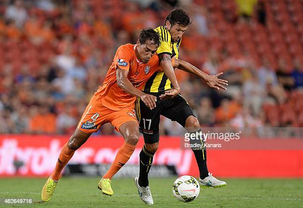 Adam Sarota of the Roar and Vince Lia of Wellington Phoenix challenge for the ball during the round 16 ALeague match between the Brisbane Roar and...