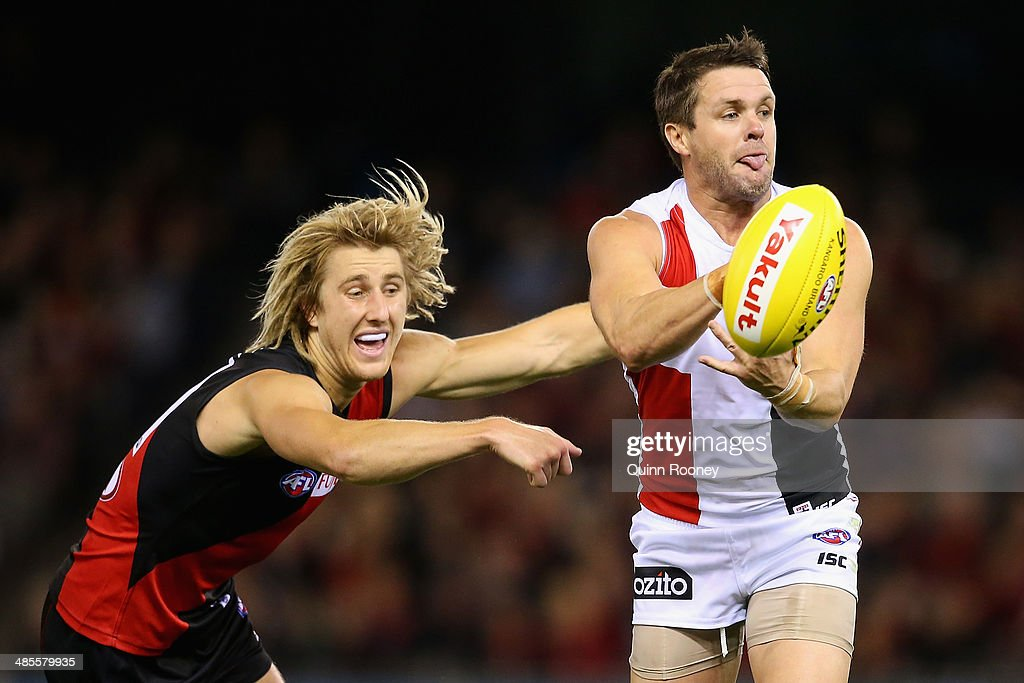 <a gi-track='captionPersonalityLinkClicked' href=/galleries/search?phrase=Adam+Schneider&family=editorial&specificpeople=541235 ng-click='$event.stopPropagation()'>Adam Schneider</a> of the Saints handballs whilst being tackled by Dyson Heppell of the Bombers during the round five AFL match between the Essendon Bombers and the St Kilda Saints at Etihad Stadium on April 19, 2014 in Melbourne, Australia.