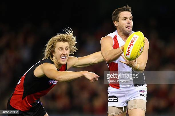 Adam Schneider of the Saints handballs whilst being tackled by Dyson Heppell of the Bombers during the round five AFL match between the Essendon...