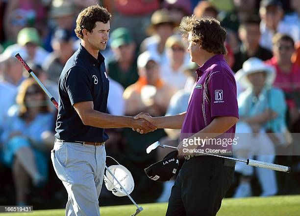 Adam Scott left shakes hands with golfer Jason Dufner following their third round in the Masters at the Augusta National Golf Club in Augusta Georgia...