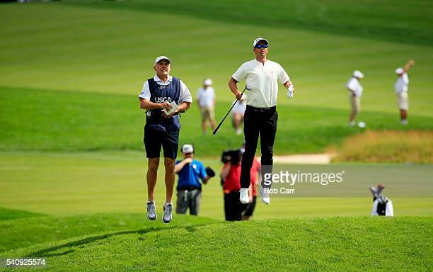 Adam Scott of Australia and caddie Steve Williams jump on the fourth hole during the continuation of the weather delayed first round of the US Open...