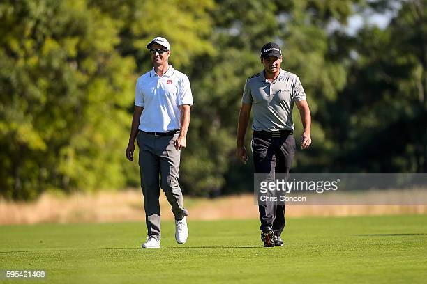 Adam Scott of Australia and Jason Day of Australia share a laugh while walking on the 13th hole fairway during the first round of The Barclays at...