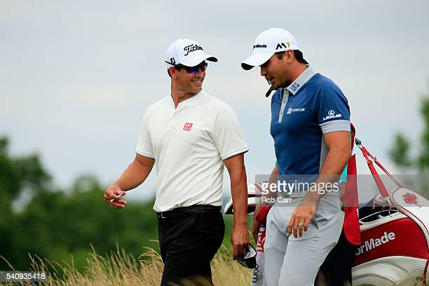 Adam Scott of Australia and Jason Day of Australia walk from the fourth tee during the continuation of the weather delayed first round of the US Open...