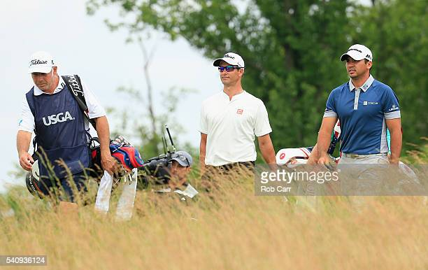 Adam Scott of Australia and Jason Day of Australia walk from the three tee during the continuation of the weather delayed first round of the US Open...