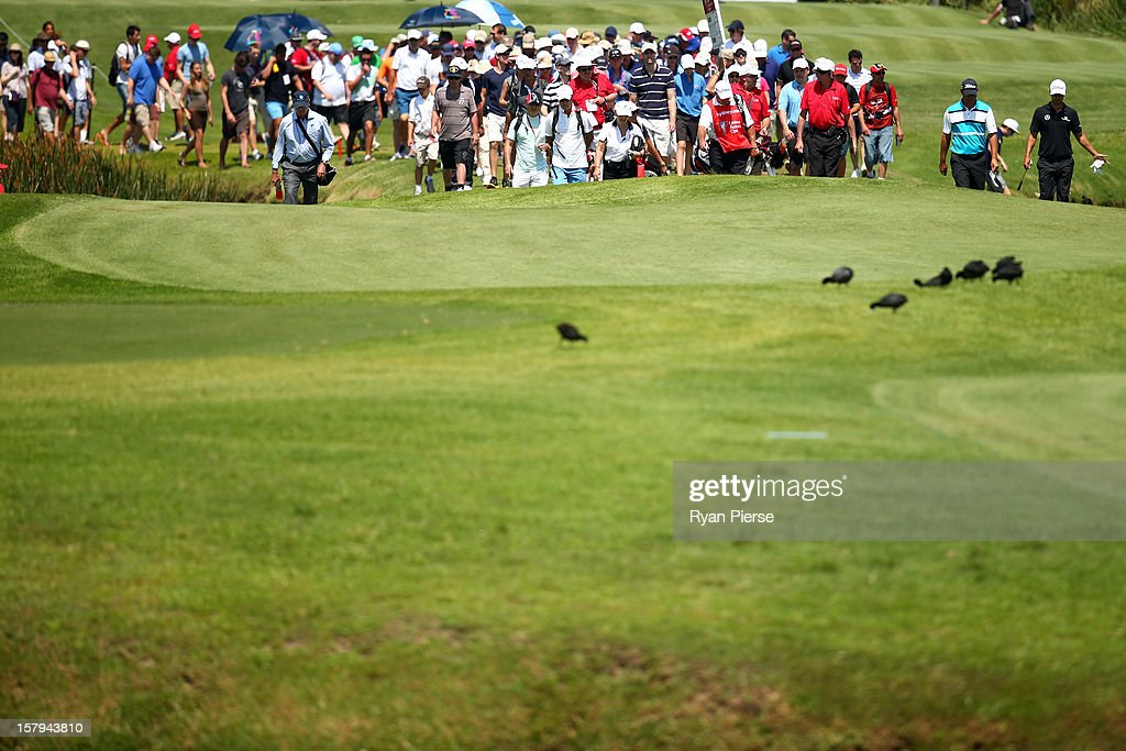 Adam Scott of Australia and Kim Felton of Australia walk down the fairway followed by the crowd during round three of the 2012 Australian Open at The Lakes Golf Club on December 8, 2012 in Sydney, Australia.