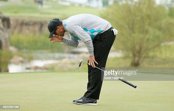 Adam Scott of Australia and the Internaional Team reacts to a putt on the 18th green during the Saturday foursomes matches at The Presidents Cup at...