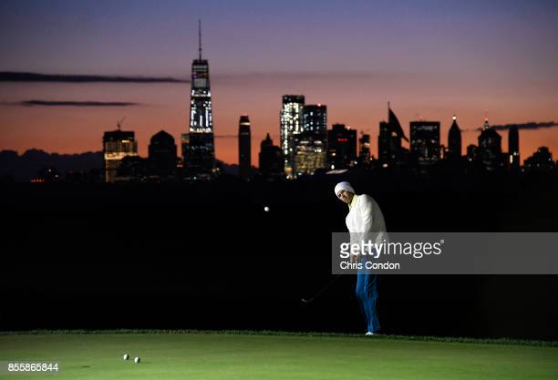Adam Scott of Australia and the International Team gets a little practice in early as the sun rises during the third round of the Presidents Cup at...