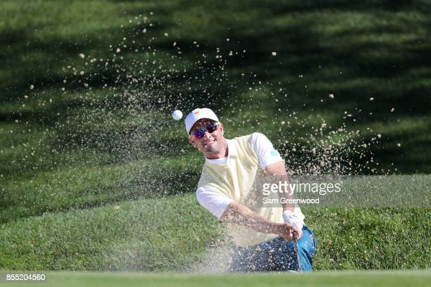 Adam Scott of Australia and the International Team plays a shot from a bunker on the fourth hole during Thursday foursome matches of the Presidents...