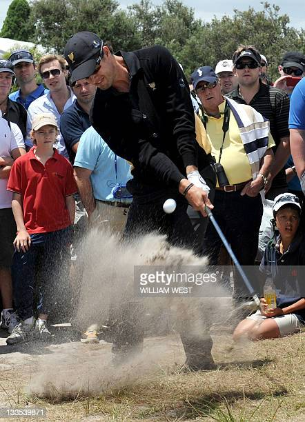 Adam Scott of Australia blasts the ball out of the rough during his match on the final day of the President's Cup golf tournament at the Royal...