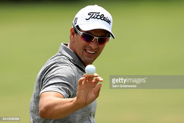 Adam Scott of Australia catches a ball on the practice range during the third round of the World Golf Championships Bridgestone Invitational at...