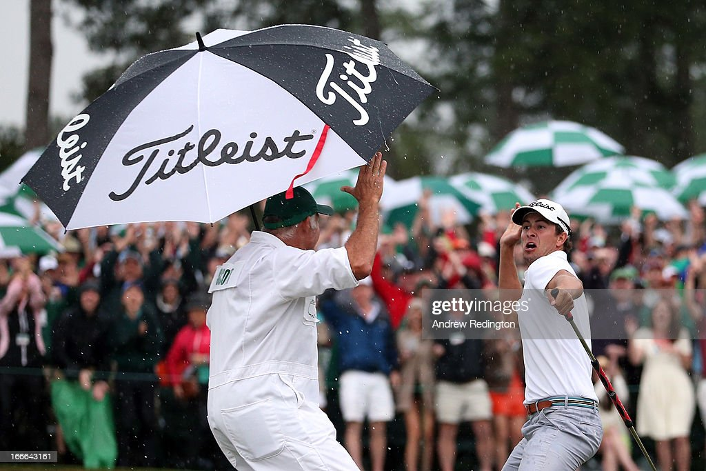 Adam Scott of Australia celebrates with caddie Steve Williams after making a birdie on the 18th hole during the final round of the 2013 Masters...