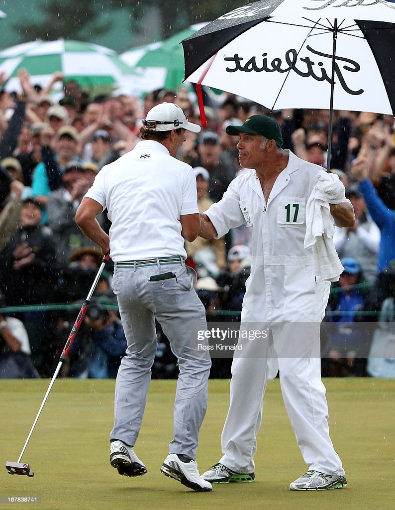 Adam Scott of Australia celebrates with his caddie Steve Williams after his birdie on the 18th green which got him into a play off during the final round of the 2013 Masters at the Augusta National Golf Club on April 14, 2013 in Augusta, Georgia.