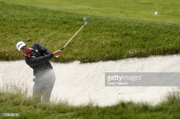 Adam Scott of Australia hits a shot from a bunker on the 15th hole during Round Two of the 113th US Open at Merion Golf Club on June 14 2013 in...