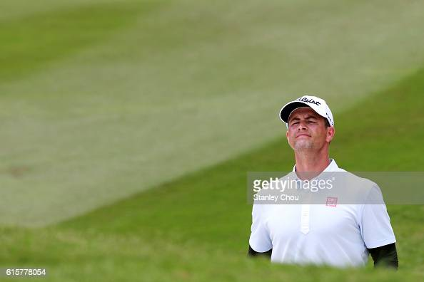 Adam Scott of Australia jumps to see the location pin hole on the 18th hole during day one of the 2016 CIMB Classic at the TPC Kuala Lumpur on...