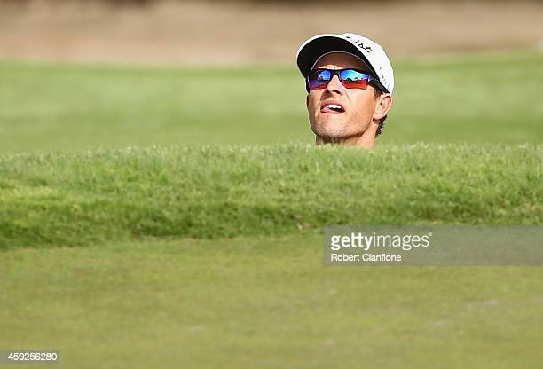 Adam Scott of Australia lines up his shot prior to playing out of the bunker during round one of the 2014 Australian Masters at the Metropolitan Golf...